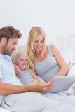 Beaux couples utilisant un ordinateur portable avec leur fille Photo stock