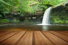 Beaux courant et cascade de région boisée en été avec le pl en bois Photos stock