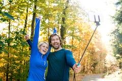 Beaux coureurs dans la forêt d'automne prenant le selfie avec le smartphone Images libres de droits