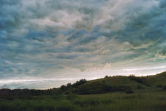 Beaux cumulus au coucher du soleil au-dessus des champs et de la vallée accidentée images libres de droits