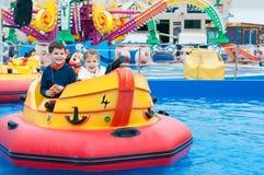 Beaux enfants ayant l'amusement à un parc d'attractions Enfants dessus Images stock