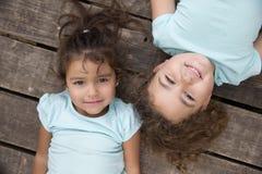 Beaux enfants dans des T-shirts bleus sur la terre en bois Photographie stock libre de droits