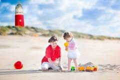 Beaux enfants de mêmes parents sur la plage à côté du phare Photos libres de droits