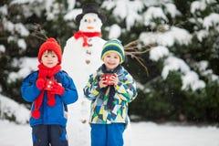 Beaux enfants heureux, frères, bonhomme de neige de construction dans le jardin photographie stock libre de droits