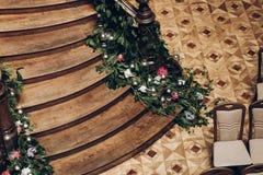Beaux escaliers en bois décorés des fleurs et du cand de verdure Image libre de droits