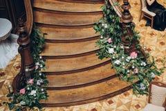 Beaux escaliers en bois décorés des fleurs et du cand de verdure Photo libre de droits