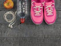 Beaux espadrilles, écouteurs, eau et pommes roses sur un plancher en bois Vue de ci-avant Photo libre de droits
