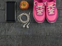 Beaux espadrilles, écouteurs, eau et pommes roses sur un plancher noir en bois Vue de ci-avant Photographie stock
