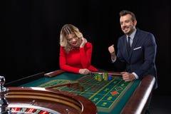 Beaux et bien habillés couples jouant la roulette dans le casino Images libres de droits