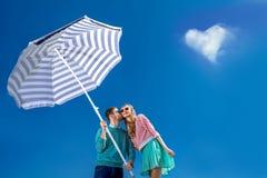 Beaux et jeunes couples embrassant avec le parapluie de plage sur s bleu Photos libres de droits