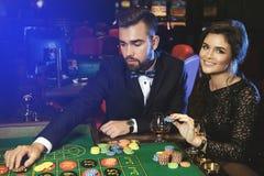 Beaux et riches couples jouant la roulette dans le casino Image libre de droits