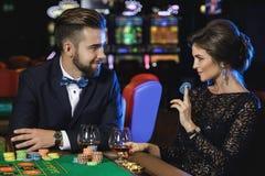Beaux et riches couples jouant la roulette dans le casino Photo stock