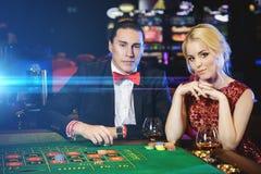 Beaux et riches couples jouant la roulette dans le casino Photos libres de droits