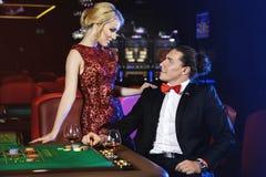 Beaux et riches couples jouant la roulette dans le casino Images libres de droits