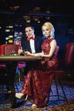 Beaux et riches couples jouant la roulette dans le casino Photographie stock libre de droits