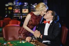 Beaux et riches couples jouant la roulette dans le casino Photos stock