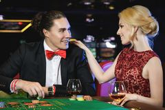 Beaux et riches couples jouant la roulette dans le casino Images stock
