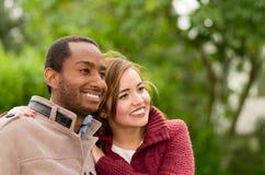 Beaux et souriants jeunes couples interraciaux heureux en parc dedans dehors Photo libre de droits