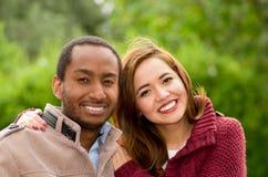 Beaux et souriants jeunes couples interraciaux heureux regardant l'appareil-photo en parc dedans dehors Photo stock