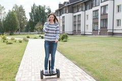Beaux faire appel et entretien de blogger de femme de brune au roulement de téléphone portable sur le scooter de compas gyroscopi photos stock