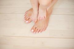 Beaux femelle et children& x27 ; pieds de s sur un plancher léger Images stock