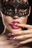 Beaux fille dans le masque avec de longs clous et sensuel Images libres de droits