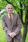 80 beaux homme supérieur an plus posant pour un portrait dans son jardin Photos libres de droits