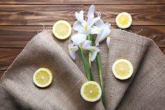 Beaux iris enveloppés dans des tranches de tissu et de citron de toile de jute sur l'OE Photo stock