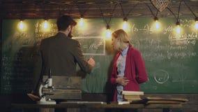 Beaux jeunes étudiants devant le grand tableau noir Tuteur aidant sa jeune étudiante avec des maths Enseignement privé clips vidéos