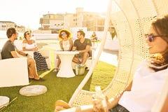 Beaux jeunes adultes ayant une vie sociale ensemble dehors sur un dessus de toit urbain Photos libres de droits