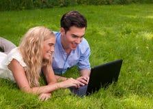 Beaux, jeunes ajouter à l'ordinateur portatif dans l'herbe Photos stock