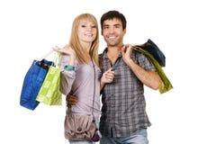 Beaux jeunes ajouter aux sacs à provisions Photo libre de droits