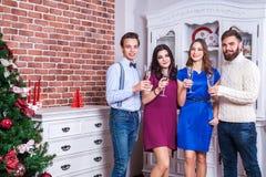 Beaux jeunes amis adultes grillant avec le champagne près de l'arbre de Noël Image libre de droits