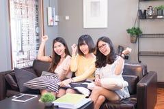 Beaux jeunes amis asiatiques de femmes employant le sourire de tablette et rire parlants Image stock