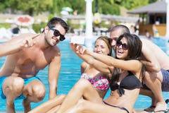 Beaux jeunes amis ayant l'amusement faisant le selfie sur la piscine Photos libres de droits