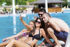 Beaux jeunes amis ayant l'amusement faisant le selfie sur la piscine Photographie stock libre de droits