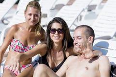 Beaux jeunes amis ayant l'amusement sur la piscine Photographie stock libre de droits