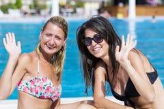 Beaux jeunes amis ayant l'amusement sur la piscine Photos stock