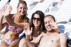 Beaux jeunes amis ayant l'amusement sur la piscine Image libre de droits