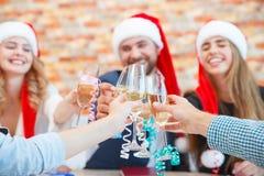 Beaux jeunes amis en gros plan faisant tinter des verres sur Noël sur un fond brouillé Concept de vacances d'hiver Photographie stock libre de droits