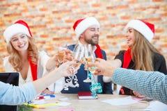 Beaux jeunes amis en gros plan faisant tinter des verres sur Noël sur un fond brouillé Concept de vacances d'hiver Photographie stock