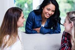Beaux jeunes amis féminins discutant dans le salon Image stock
