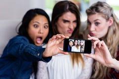Beaux jeunes amis féminins prenant le selfie Photo stock