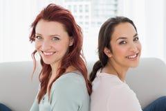 Beaux jeunes amis féminins s'asseyant à la maison Photos libres de droits