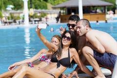 Beaux jeunes amis riant et faisant le selfie sur la piscine Photos libres de droits