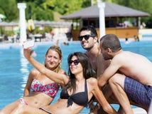 Beaux jeunes amis riant et faisant le selfie sur la piscine Image stock
