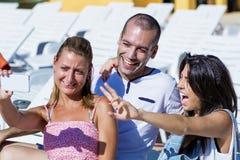 Beaux jeunes amis riant et faisant le selfie sur la piscine Images stock