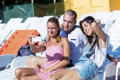 Beaux jeunes amis riant et faisant le selfie sur la piscine Image libre de droits