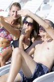 Beaux jeunes amis riant et faisant le selfie sur la piscine Photographie stock
