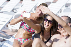 Beaux jeunes amis riant et faisant le selfie sur la piscine Photo stock